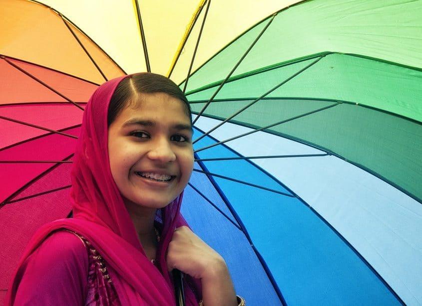 smiling girl holding umbrella